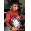 Ahmad Sobirin, orang tua salah satu korban serangan DBD, menunjukkan foto anaknya.
